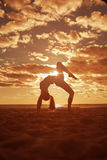 Young beautiful slim woman silhouette practices yoga on beach Royalty Free Stock Photos