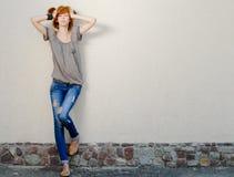 Young beautiful slim woman standing near gray wall Stock Photo
