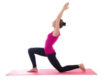 Young beautiful slim woman standing on pink mat in yoga pose iso Stock Photo