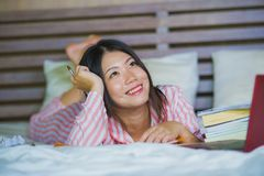 Young cute and happy nerdy Asian Korean student teenager girl in nerd glasses and hair ribbon studying at home bedroom sitting on stock photo