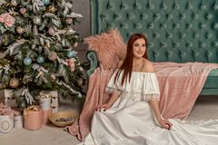 Young beautiful smile woman in white elegant evening dress sitting on floor near christmas tree and presents. Interior with christ. Young beautiful smile woman Royalty Free Stock Photography