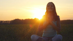 Young beautiful smiles woman meditates in nature, in the field during amazing sunset with lense flare effects Royalty Free Stock Image