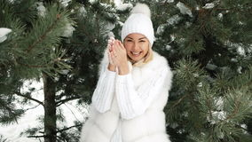 Young beautiful smiling blonde blast snow with her hands. stock footage