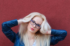 Young beautiful smiling blonde girl with beautiful appearance and long hair. Smiling girl in glasses and a charming look. Royalty Free Stock Images