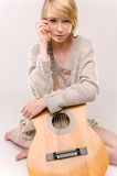 Young beautiful smiling blonde lady in gray sweater playing acoustic guitar. Picture presents young beautiful smiling blonde lady in gray sweater playing Stock Images