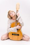 Young beautiful smiling blonde lady in gray sweater playing acoustic guitar Stock Images