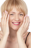Young beautiful smiling  blonde woman. Covers her face with her hands  closeup Stock Photography
