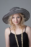 Young beautiful smiling  blonde woman. In a hat  and a black dress looking and posing for the camera Stock Images