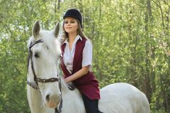 Brunette woman riding dark horse at summer green forest. Young beautiful smiling brunette woman wearing white dress riding dark horse at summer green forest Stock Image