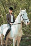 Brunette woman riding dark horse at summer green forest. Young beautiful smiling brunette woman wearing white dress riding dark horse at summer green forest Royalty Free Stock Photos