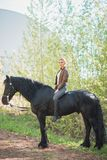 Brunette woman riding dark horse at summer green forest. Young beautiful smiling brunette woman wearing white dress riding dark horse at summer green forest Royalty Free Stock Images