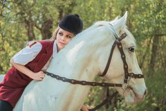 Brunette woman riding dark horse at summer green forest. Young beautiful smiling brunette woman wearing white dress riding dark horse at summer green forest Stock Photo