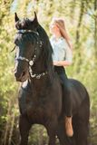Brunette woman riding dark horse at summer green forest. Young beautiful smiling brunette woman wearing white dress riding dark horse at summer green forest Stock Photos