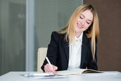 Smiling business woman office workspace manager. Young beautiful smiling business woman. successful stylish company manager in office workspace Royalty Free Stock Photo