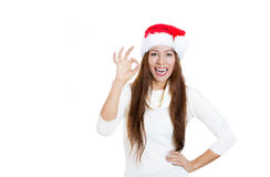 young, beautiful smiling christmas girl in red santa hat, giving ok sign Stock Photos