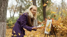 Blonde girl artist draws among falling leaves in the autumn park stock photos