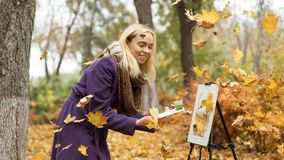 Blonde girl artist draws among falling leaves in the autumn park royalty free stock photos