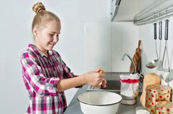Young beautiful smiling girl breaks an egg into deep dish. Cute blonde cooking in a home kitchen royalty free stock photos