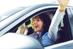 Young beautiful smiling girl driving a car. Young beautiful smiling girl driving a new car stock images