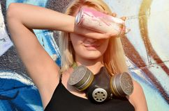 Young and beautiful smiling girl graffiti artist with gas mask on her neck hiding his eyes with a spray can. Standing on a wall background with a graffiti royalty free stock photography