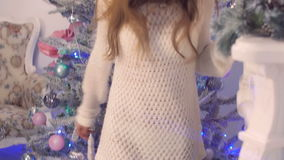 Young beautiful smiling girl in a knitted sweater over her naked body dancing and singing near the Christmas tree stock video footage