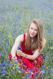 Young beautiful smiling girl picking flowers in the meadow. Outdoor portrait Stock Image