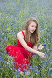 Young beautiful smiling girl picking flowers in the meadow. Outdoor portrait Royalty Free Stock Photo
