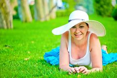 Young beautiful smiling girl relaxing on the lawn in white hat Stock Images