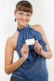 Young beautiful Smiling girl shows a business card. Young beautiful confident girl with glasses and in a blue blouse keeps in the hands a business card. She Stock Photos