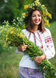 Young beautiful smiling girl in Ukrainian costume with a wreath. On his head in a meadow Royalty Free Stock Image