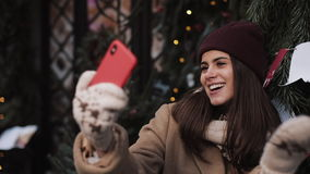 Young Beautiful Smiling Girl Wearing Winter Clothes, Posing, Waving, Blowing a Kiss Making Selfie or Video Message stock video footage