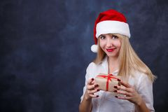 Young beautiful smiling happy woman in Santa cap with a gift box. In hands on studio background, free space for text design. New Year, Christmas, gift, surprise Stock Photo