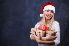Young beautiful smiling happy woman in Santa cap with many gift. Boxes in hands on studio background, free space for text design. New Year, Christmas, gift Royalty Free Stock Image