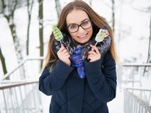 Young beautiful smiling young woman strolling in wintertime outdoor holding delicious marshmallow candy Royalty Free Stock Photography