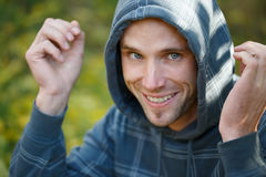 Young beautiful smiling man in sports wear and hood on head with Stock Images