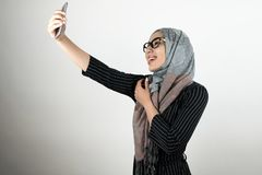 Young beautiful smiling Muslim woman in glasses wearing turban hijab, headscarf holding smartphone shooting a selfie stock image