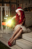 Young beautiful smiling santa woman. Christmas Fashionable luxur Stock Photo