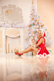 Young beautiful smiling santa woman near the Christmas tree with. Bunny. Fashionable luxury  girl celebrating New Year Stock Photo