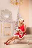 Young beautiful smiling santa woman near the Christmas tree with Royalty Free Stock Photo