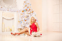 Young beautiful smiling santa woman near the Christmas tree with Stock Photo