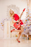 Young beautiful smiling santa woman near the Christmas tree with. Bunny. Fashionable luxury  girl celebrating New Year with electric guitar Stock Images