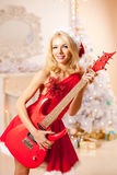 Young beautiful smiling santa woman near the Christmas tree with Stock Photography