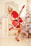 Young beautiful smiling santa woman near the Christmas tree with Royalty Free Stock Photos