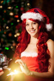 Young beautiful smiling santa woman near the Christmas tree with Royalty Free Stock Images