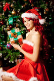 Young beautiful smiling santa woman near the Christmas tree with Stock Images