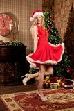 Young beautiful smiling santa woman near the Christmas tree. Fas Royalty Free Stock Images