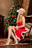 Young beautiful smiling santa woman near the Christmas tree. Fas Stock Images