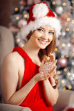 Young beautiful smiling santa woman near the Christmas tree. Fas Stock Photos