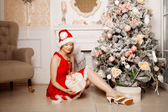 Young beautiful smiling santa woman near the Christmas tree. Fas Stock Photography