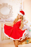 Young beautiful smiling santa woman near the Christmas tree. Gir Royalty Free Stock Photography